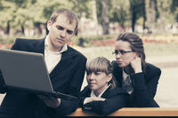 Young business people using laptop in city park