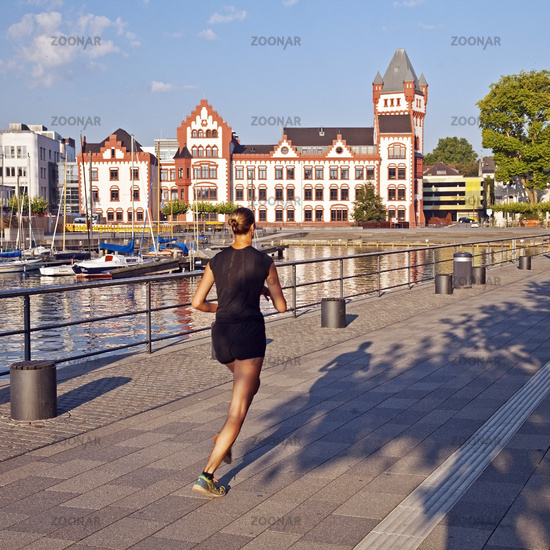 female jogger with castle Hoerde at Phoenix Lake, Dortmund, North Rhine-Westphalia, Germany, Europe