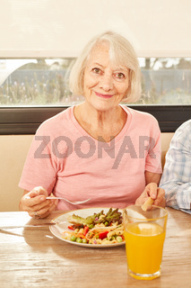 Seniorin isst Salat und trinkt Orangensaft