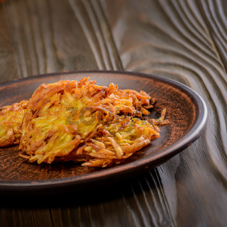 Fresh homemade tasty potato pancakes in clay dish on rustic wooden table