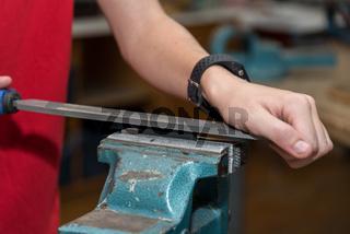 Handwerker bearbeitet mit Feile ein Metallstück am Schraubstock - Nahaufnahme