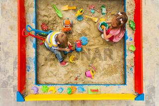 Kids having fun in big modern sandbox outside