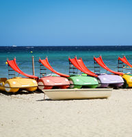 Pedal boats with slide lie on the beach