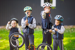 Children mechanics, bicycle repair. Happy kids fixing bike together outdoors in sunny day. Bicycle repair concept. Teamwork family posing with tools for repairing a bicycle in hands outside