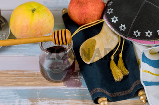 Apple and honey, traditional food of jewish New Year Rosh Hashana torah book, kippah yamolka talit