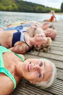 Gruppe Senioren liegt entspannt am Badesee
