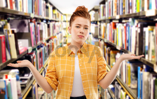 sad red haired student girl shrugging at library