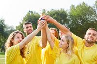 Sieger Team hält stolz den Pokal hoch