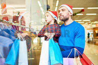 Man with daughter shopping in Christmas time