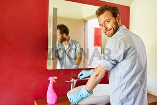 Hausmann putzt Waschbecken mit Schwamm