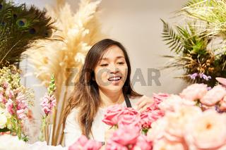 Asiatische Frau arbeitet im eigenen Blumenladen