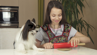 Teen girl and dog Papillon prepare cookies, rolling dough with rolling pin