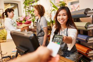 Kassiererin nimmt Kreditkarte zum Bezahlen