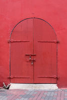 Old style Arched top wooden door painted in dark red set in red wall.