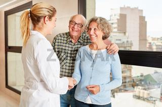 Ärztin beim Hände schütteln mit Senioren Paar