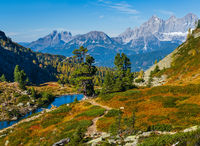 Sunny autumn alpine view. Peaceful mountain forest lake with clear transparent water and reflections. Spiegelsee or Mittersee or Mirror Lake