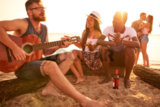 Talented guitarist playing guitar for friends on beach