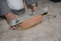 Bricklayer works with brick and mortar with the help of a spirit level - close-up