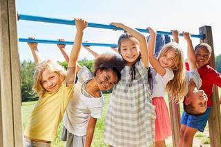 Multikulturelle Kinder turnen auf Sportgerät