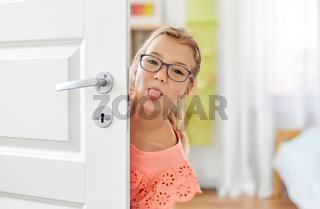 girl behind door showing her tongue at home