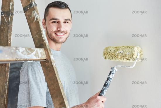 Junger Mann beim Wände streichen und grundieren