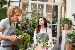 Junge Floristin und Kollege binden Blumenstrauß