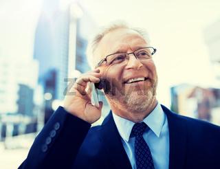 smiling old businessman calling on smartphone