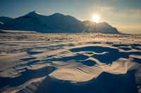 Arctic winter landscape with snow covered mountains at Kapp Ekholm, Svalbard, Norway, backlit