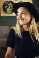 Attractive cute caucasian girl in black tshirt and black hat