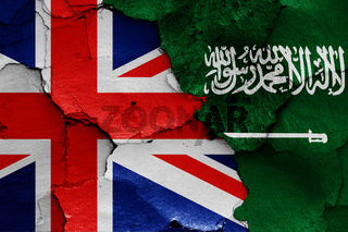 flags of UK and Saudi Arabia painted on cracked wall