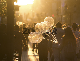 Young woman with balloons walking in crowd on the pedestrian street at summer sunset