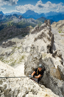 attractive female climber on a steep Via Ferrata in the Italian Dolomites