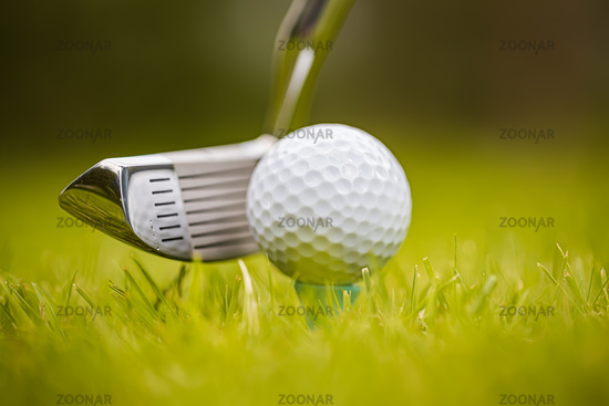 Golf ball on tee in front of driver