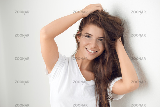 Young smiling brünette woman leaning against wall
