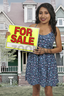 Woman holding for sale sign