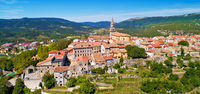 Buzet. Hill town of Buzet surrounded by stone walls in green landscape aerial panoramic view