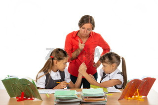 Teacher scolding schoolgirls fighting at a desk