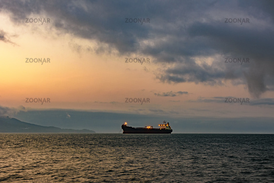 Cargo ship anchored in the waters of Ilhabela Island at sunset