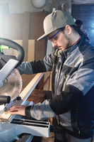 Young brunette man wearing a cap in a gray jacket by profession a carpenter cuts wooden boards with a circular saw on a workbench table in a workshop. Professional equipment in home workshops