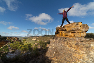 Female hiker on top of a pagodas after climbing up with views