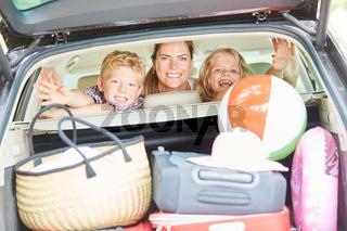 Mutter und Kinder im Auto mit viel Gepäck
