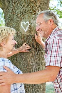 Senioren Paar vor Baum mit Kreide Herz