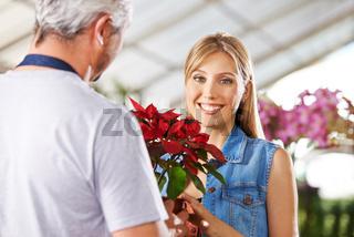 Frau kauft Weihnachtsstern im Blumenladen