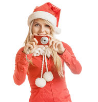 Beautiful smiling young woman in Santa Claus hat and red shirt with camera