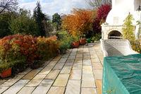 Terrasse aus Naturstein an einem Wohnhaus mit abgedekten Gartenmöbeln