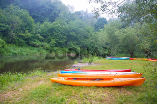 ten kayaks near the river, double kayaks on the shore