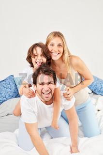 Eltern albern vergnügt mit ihrem Sohn im Bett