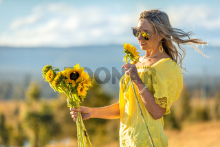 Happy woman holding sunflowers hair blowing in the wind