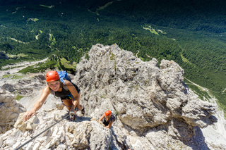 two women mountain climbers on an exposed Via Ferrata in the Dolomites of Italy