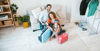 Happy family going on vacation, sitting on couch with suitcases.